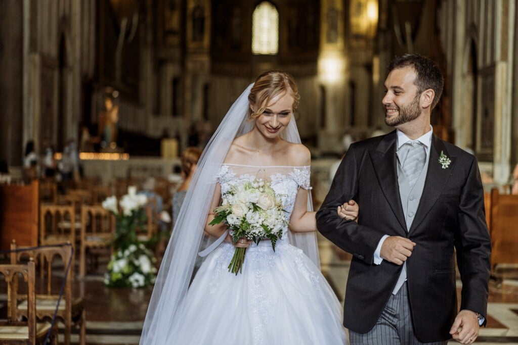Bride and Groom into Cathedral  in elegant destination wedding in Sicily