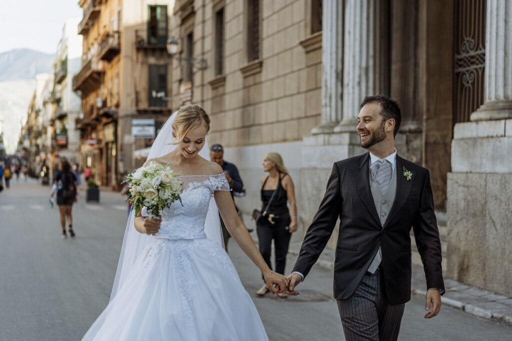 Bride and Groom walk into the Palermo center in elegant destination wedding in Sicily