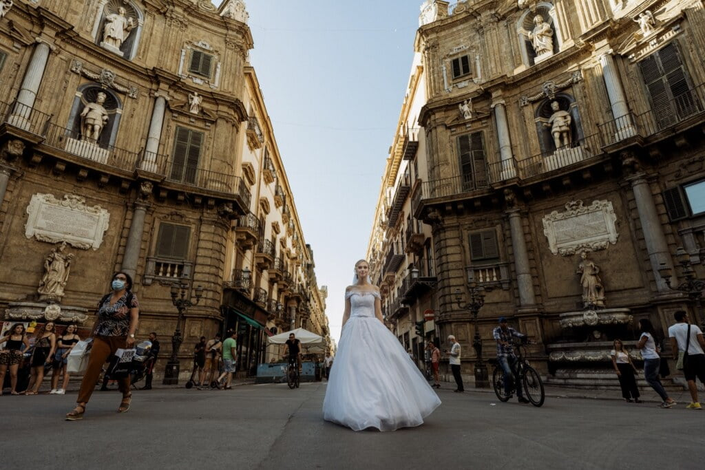 Bride walk into Palermo center in elegant destination wedding in Sicily